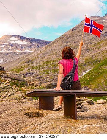 Tourist Woman Holds Norwegian Flag, Enjoying Nature Landscape From Trollstigen Viewpoint Area. Troll