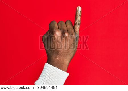 Arm and hand of african american black young man over red isolated background showing little finger as pinky promise commitment, number one
