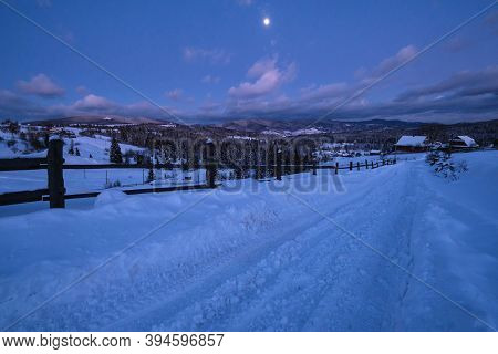 Night Countryside Road, Hoases, Hills, Groves And Farmlands In Winter Remote Alpine Mountain Village