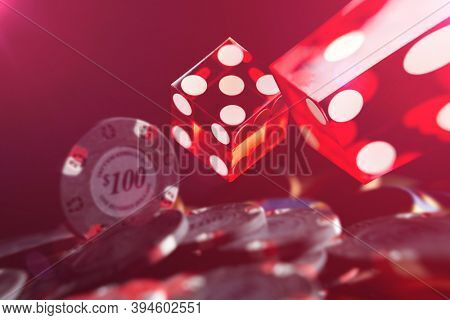 Rolling red dices and Casino chips on a gaming table