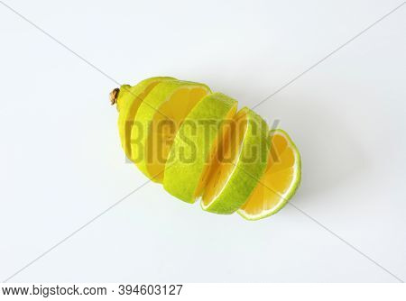 Lemon with green peel and yellow flesh, sliced