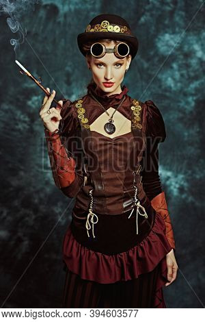 Steampunk concept. Portrait of a beautiful confident steampunk girl smoking a cigarette in the mouthpiece on a vintage background.