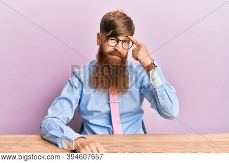 Young irish redhead man wearing business shirt and tie sitting on the table pointing unhappy to pimple on forehead, ugly infection of blackhead. acne and skin problem
