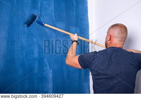 Young happy man painting interior wall with paint roller in new house. Home decoration concept.