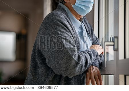 Senior woman wearing face mask standing at window and looking outside during covid-19 pandemic. Old sad woman wearing  surgical mask and looking out of window during coronavirus quarantine.