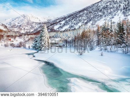 Fabulous Winter Scenery With Frozen River With Wooden Houses And Snow Covered Pine Trees Near Valber