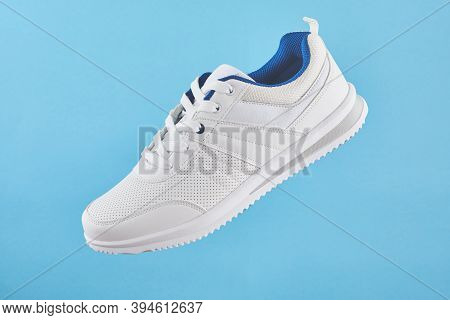 White Sports Sneakers Levitate On A Blue Background. Stylish Man Sneakers For Fitness.