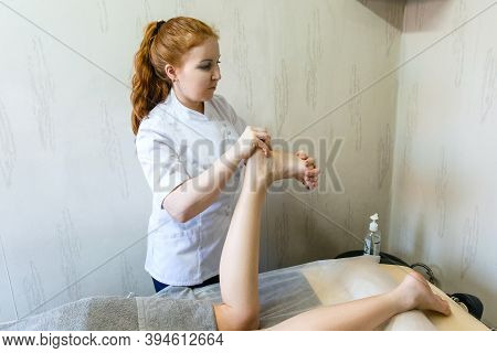 The Masseur Therapist Conducts A Therapeutic Foot Massage To Restore Strength And Health Of Female L