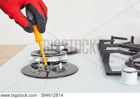 Repairs And Fixing Of Gas Control Panel. Man Hand In Protective Gloves Repairs Hotplate Of Hob.