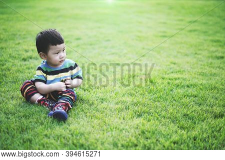 Portrait Kid Sit And Thinking In The Garden. Portrait Little Boy With Thinking Idea Space.