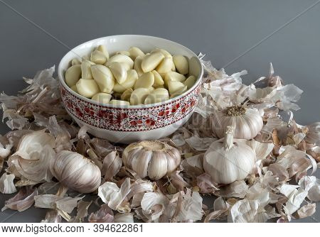 Garlic Is In The Plate. The Husk From The Garlic On A Gray Background