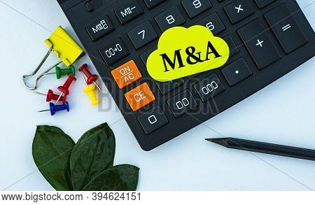 M&a (mergers And Acquisitions) - Word On Yellow Note Sheet On White Background With Calculator, Penc