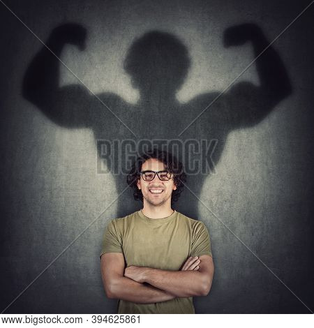 Confident Young Man Shadows Transforms Into A Muscular Person On The Wall As Metaphor For Inner Stre