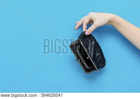 Female Hand Holding Empty Wallet On Blue Background With Copy Space. Lack Of Money. Poverty And Bank