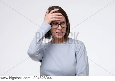Mature Caucasian Woman Has A Terrible Headache, Isolated On White Wall.