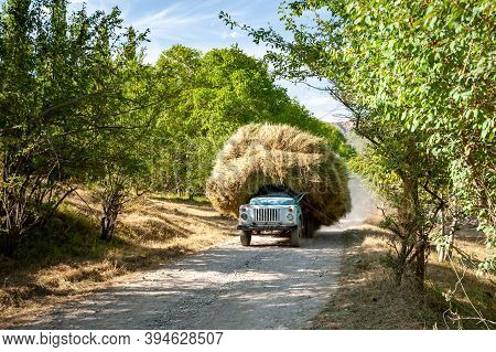 Old Soviet Truck Full Of Hay. Tractor Full With Bale Hay On Village Road Near Sary Chelek Lake, Sary