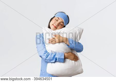 Kawaii Asian Girl In Sleeping Mask And Pajamas Hugging Comfortable Pillow With Closed Eyes. Woman In