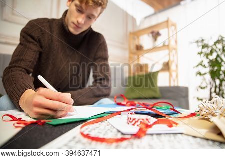 Young Man Making Greeting Card For New Year And Christmas 2021 For Friends Or Family, Scrap Booking,