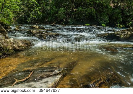 Fast Moving River Flowing Downstream From The Mountains With Whitewater Cascading Through Rocks And