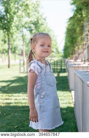 Little Girl Blonde 5 Years Old In Denim Sarafan Walks Around The Park
