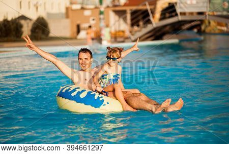 Father Playing With His Daughter In Swimming Pool. Funny Family Weekend.