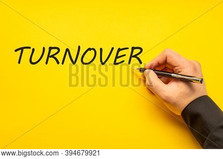 Male Hand Writes In Black Pen The Word Turnover On A Yellow Background With Copy Space. Business Con