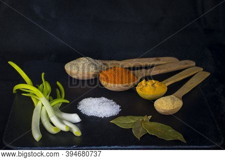 Wooden Spoons With Multicolored Spices Fragrant Seasonings Pepper Green Onion Salt And Bay Leaf