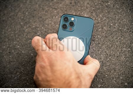 Paris, France - Nov 11, 2020: Man Placing Charging Device Magsafe Wireless Charger The Latest Iphone