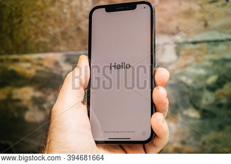 Paris, France - Nov 11, 2020: Hallo German Hello Word In As Man Hand Holding New Iphone 12 Pro Max 5