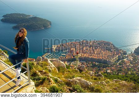 Attractive Brunette Traveller Sitting On A Railing Above The City Of Dubrovnik, Viewpoint On Srd Mou