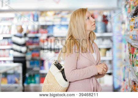 Young Caucasian woman with handbag shopping at supermarket