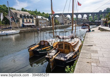 Dinan, France - August 26, 2019: Sailboats Moored In Port Of Dinan On The Rance River And Viaduct Of