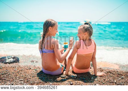 Uv Protection. Sister Puts Sunscreen On Her Little Sisters Nose