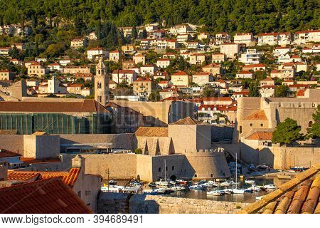 Bay Area In The Port Of Dubrovnik, Waterside Of The City Walls. Boats Anchored And A Church Belltowe