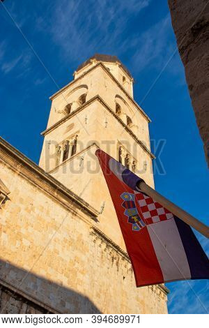 Vertical Shot Of A Croatian Flag Waving In The Wide Beneath A Church Tower In The Old City Of Dubrov