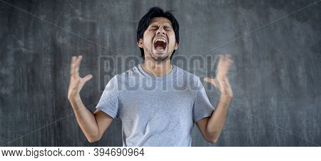 Portrait young asian man Crazy and angry emotions against gray wall background with copy space
