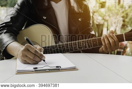 A Song Writer Holding Pen For Compose A Song. Musician Playing Acoustic Guitar. Live Music And Abstr