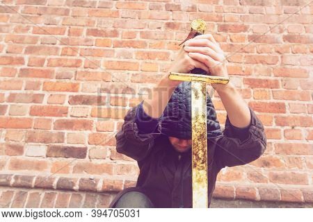 Warior Man With Golden Sword. Man Kneels In A Hooded Cloak. Assassin Swears Allegiance