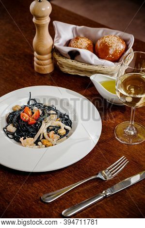 Black Spaghetti. Spicy Black Seafood Pasta With Squid With Basil On Wooden Table.