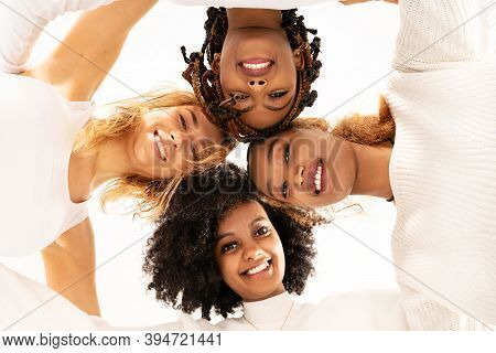 Group Of Four Happy Multiethnic Friends Looking At Camera. Portrait Of Young Women Of Different Cult
