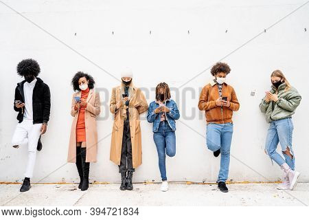 Multiracial People Looking At Mobile Phones With Mask On Faces. Young People Lifestyle During Pandem