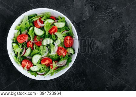 Healthy Green Salad With Fresh Tomato, Cucumber, Red Onion And Lettuce In Bowl On Dark Stone Backgro