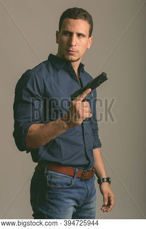 Thoughtful Young Muscular Persian Man Standing While Holding Gun Ready For Action Against Gray Backg