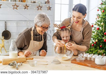Merry Christmas and Happy Holidays. Family preparation holiday food. Grandma, mother and daughter cooking cookies.