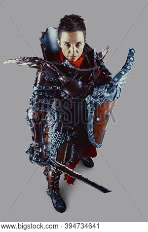 Portrait Of A Medieval Female Knight In Armor With A Sword And Shield In Hands. Isolated Over Grey B
