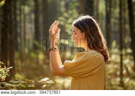 nature, spirituality and supernatural concept - young woman or witch performing magic ritual in forest