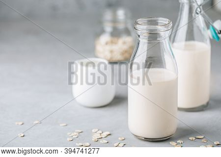 Oat Milk In Glass. Vegan Non Dairy Oat Milk On Gray Stone Background