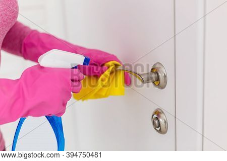 Woman Cleaning A Door Handle With A Disinfection Spray And Disposable Wipe. Woman Sanitizing Door Ha