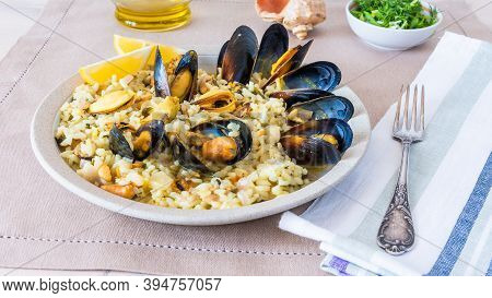 Mediterranean Dish - Risotto, Pilaf With Mussels In A Plate With Lemon Slices Close-up, Italian, Gre