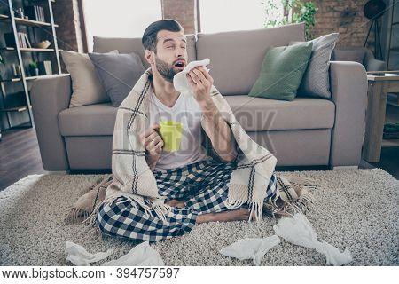 Photo Of Handsome Guy Homey Sit Floor Sofa Quarantine Stay Home Covered Blanket Drink Hot Medicine B